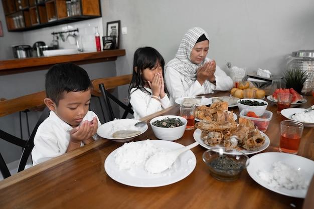 Famiglia musulmana che prega. prima di mangiare Foto Premium