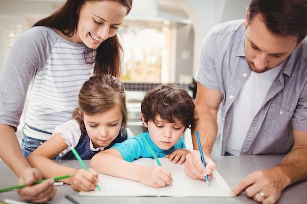 Famiglia scrivendo nel libro, mentre in piedi al tavolo Foto Gratuite
