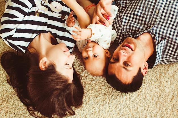 Famiglia sdraiata sul tappeto Foto Gratuite