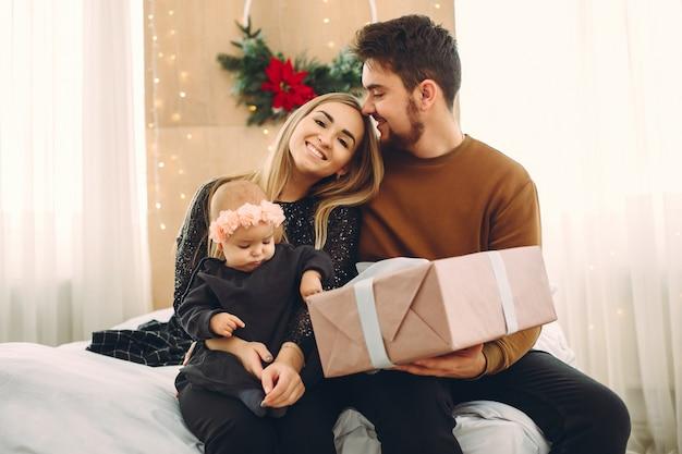 Famiglia seduto a casa su un letto con regali Foto Gratuite