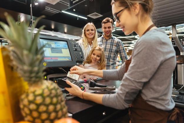 Famiglia sorridente che paga con una carta di credito Foto Gratuite