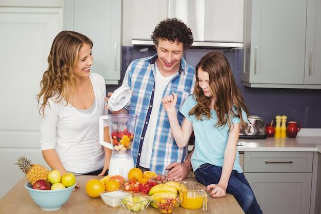 Famiglia sorridente che prepara il succo di frutta Foto Premium