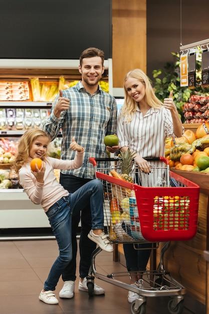 Famiglia sorridente che sceglie la spesa Foto Gratuite