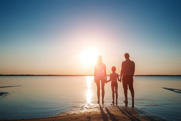 Famiglia sul lago contro un bel tramonto. Foto Premium