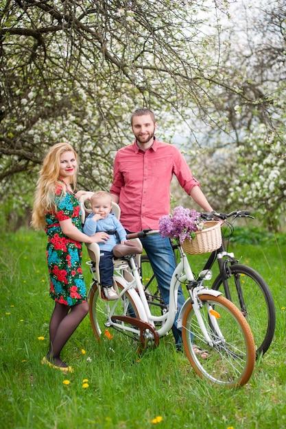 Famiglia sulle biciclette nel giardino di primavera Foto Premium