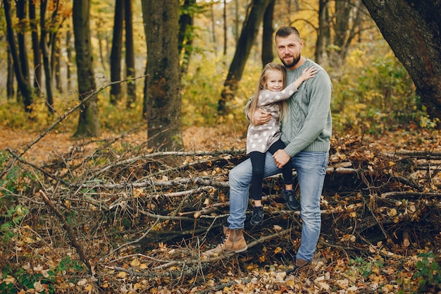 Famiglia sveglia che gioca in un parco di autunno Foto Gratuite
