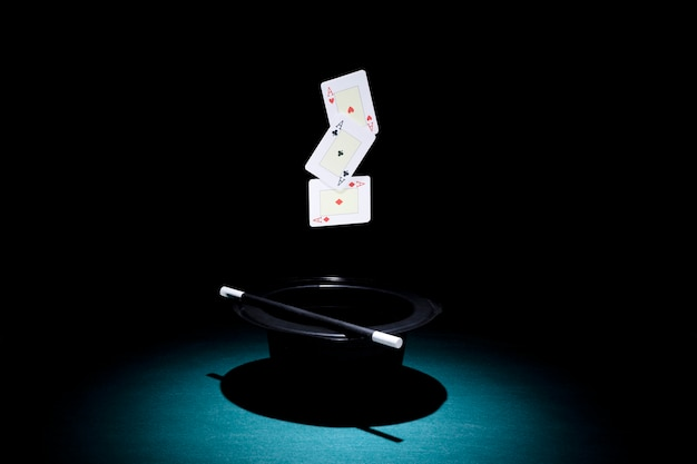 Far luce sul cappello con una carta da gioco di tre assi Foto Gratuite