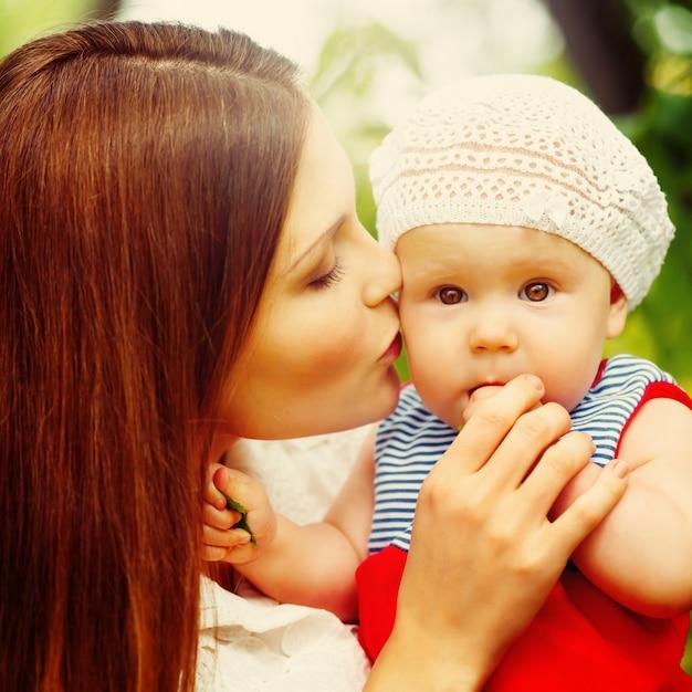 Fare da baby-sitter sveglio del bambino sulle mani del `s della mamma Foto Premium