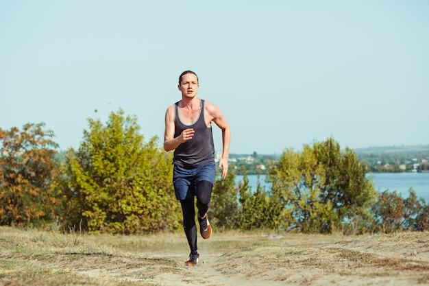 Fare sport. sprint corridore uomo all'aperto nella natura scenica. traccia muscolare adatta di addestramento dell'atleta maschio che corre per la corsa di maratona. uomo atletico in forma sportiva che risolve in abbigliamento di compressione in volata Foto Gratuite