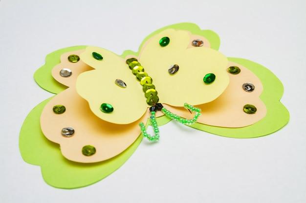 Farfalla verde gialla fatta di carta colorata, paillettes multicolori, paillettes e perline Foto Premium