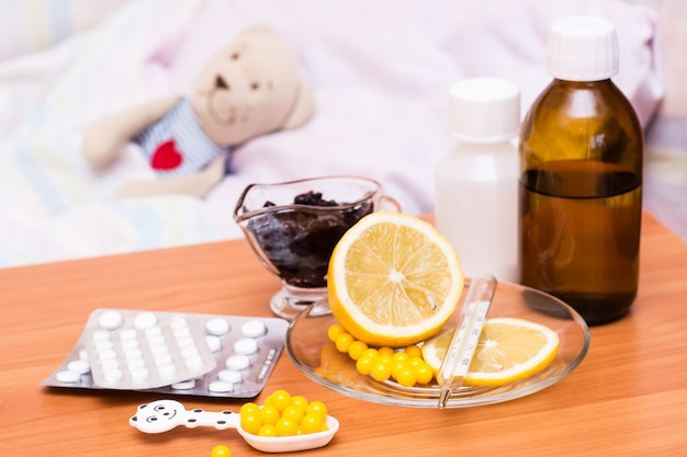 Farmaci, vitamine, limone e marmellata sul letto per bambini con un peluche Foto Premium