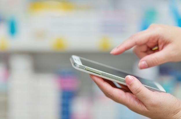 Farmacista che utilizza smart phone mobile per la barra di ricerca su esposizione nel fondo degli scaffali della farmacia della farmacia concetto medico online. Foto Premium