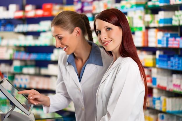 Farmacista con assistente in farmacia Foto Premium