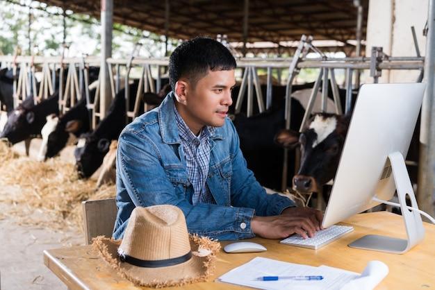 Farmer sta usando il computer per informazioni sulla fattoria. vendere latte online Foto Premium