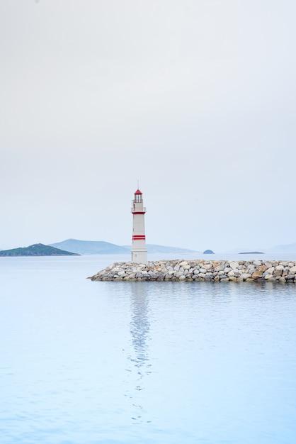 Faro solitario su una strada di pietra in mezzo al mare con vista sulle montagne e nebbia Foto Premium