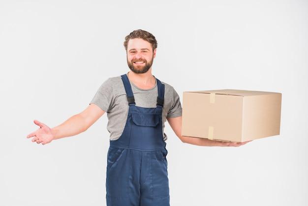 Fattorino allegro che sta con la grande scatola Foto Gratuite