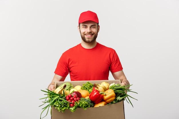 Fattorino caucasico bello che porta la scatola del pacchetto di alimento e bevande del drogheria dal deposito. Foto Premium