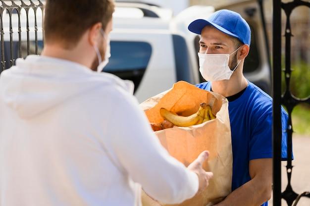 Fattorino che distribuisce generi alimentari al cliente Foto Gratuite