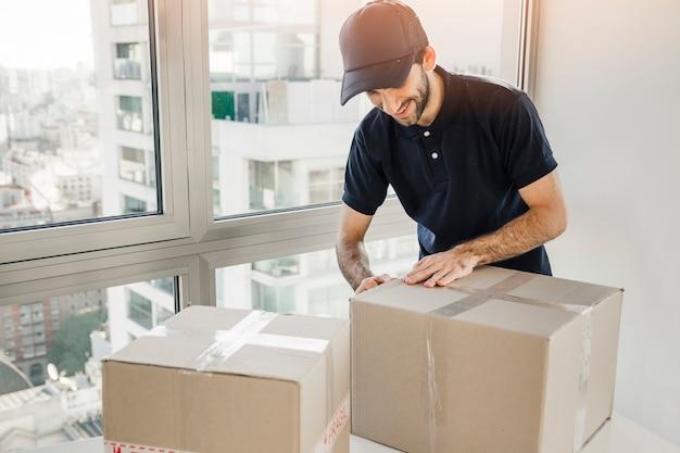 Fattorino che prepara pacco per la spedizione ai clienti Foto Gratuite