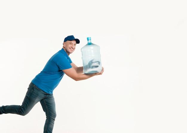 Fattorino che sorride e che posa con la bottiglia di acqua Foto Gratuite
