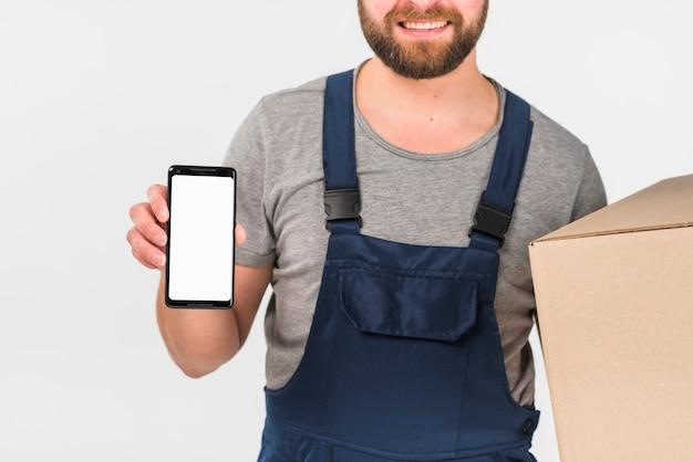 Fattorino che tiene grande scatola e smartphone con lo schermo in bianco Foto Gratuite