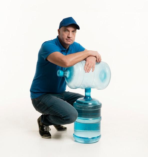 Fattorino con il cappuccio che posa con le bottiglie di acqua Foto Gratuite