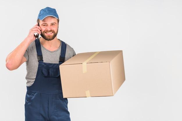 Fattorino con scatola parlando per telefono Foto Gratuite