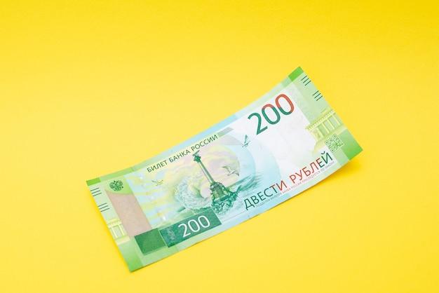 Fattura da duecento rubli su uno sfondo di carta gialla. Foto Premium