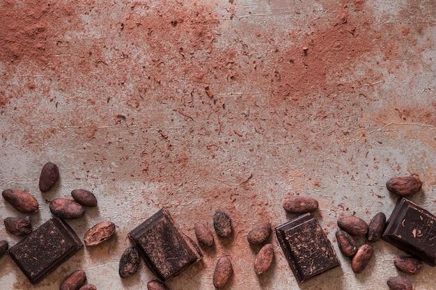 Fave di cacao e polvere con pezzi di barretta di cioccolato su un vecchio fondo Foto Gratuite