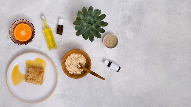 Favo; avena; olio essenziale; pianta di cactus; argilla rhassoul; agrumi tagliati a metà su sfondo bianco con texture in cemento Foto Gratuite