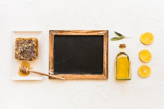 Favo, olio d'oliva e fette di limone con mestolo e ardesia vuota Foto Gratuite