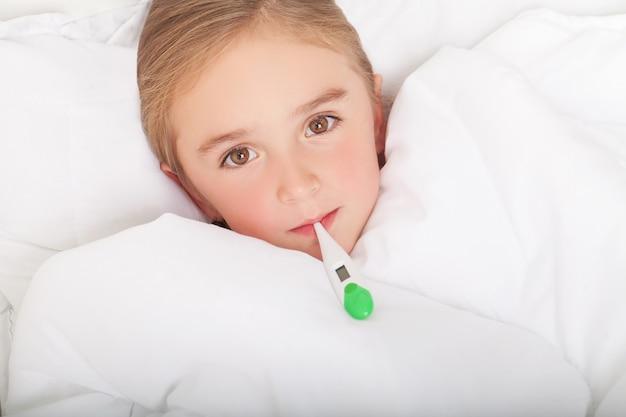 Febbre, raffreddore e influenza - medicinali e tè caldo in una ragazza vicina e malata a letto Foto Premium