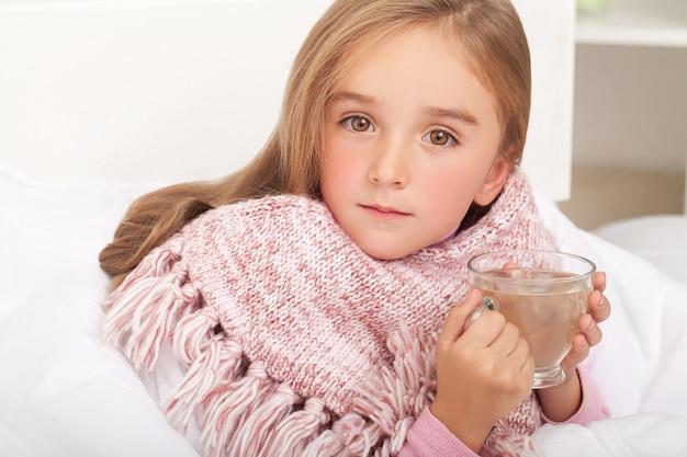 Febbre, raffreddore e influenza medicinali e tè caldo nel vicino, ragazza malata a letto Foto Premium