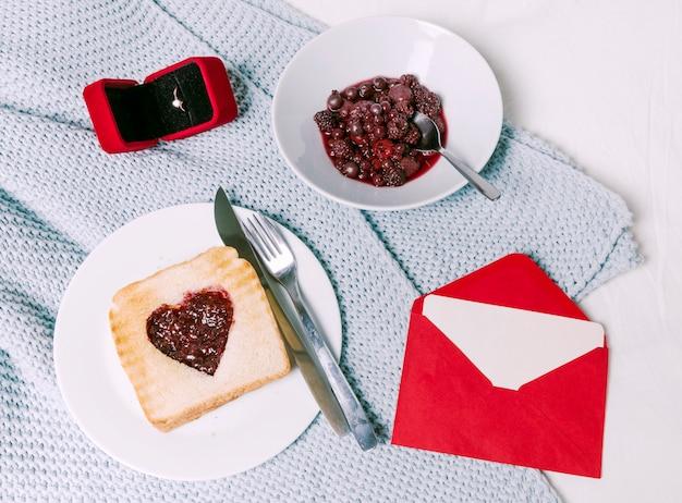Fede nuziale con pane tostato con marmellata a forma di cuore sulla sciarpa Foto Gratuite
