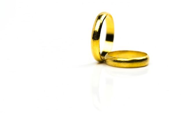 Fede nuziale dell'oro due isolata su bianco con lo spazio della copia Foto Premium