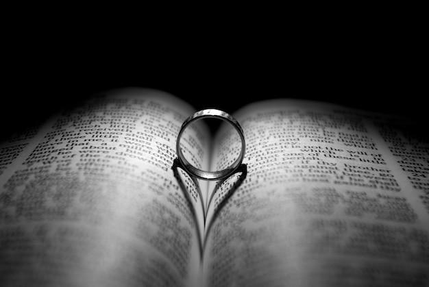 Fede nuziale sul libro, la sua ombra ha la forma di un cuore Foto Premium