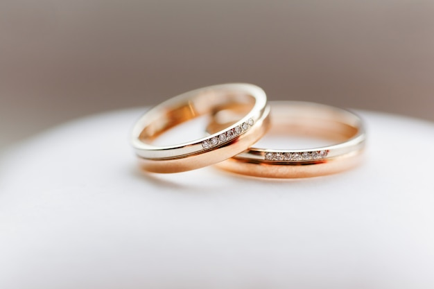 Fedi nuziali dorate con i diamanti su fondo bianco. simbolo di amore e matrimonio. Foto Premium