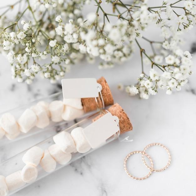 Fedi nuziali dorate; provette di fiori e di marshmallow con etichetta bianca Foto Gratuite
