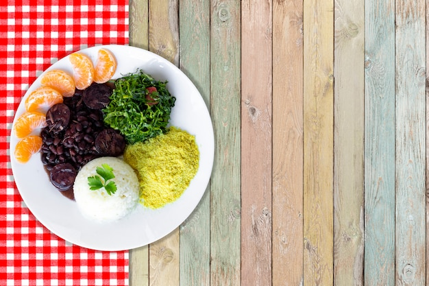 Feijoada brasiliana. con uno sfondo in legno vista dall'alto - immagine Foto Premium