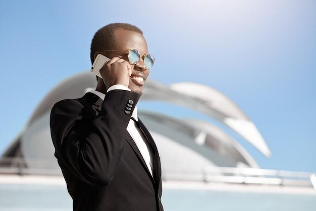 Felice allegro uomo d'affari nero in abiti formali e occhiali da sole parlando su smartphone fuori dall'ufficio builing al mattino presto, fissare un appuntamento per un incontro di lavoro con potenziali partner Foto Gratuite