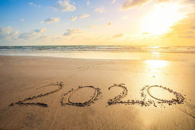 Felice anno nuovo 2020 testo sulla bellissima spiaggia del mare con onda alba del primo mattino sopra l'orizzonte Foto Premium