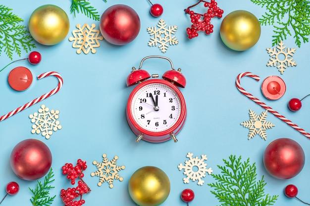 Felice anno nuovo piatto composizione laici, decorazioni di natale orologio su sfondo blu Foto Premium
