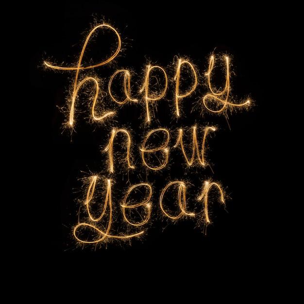 Felice anno nuovo scritto con i fuochi d'artificio sparkle Foto Premium