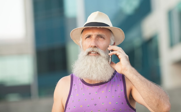 Felice anziano uomo barbuto turista sorridente e ridacchiando mentre si utilizza il telefono cellulare Foto Premium