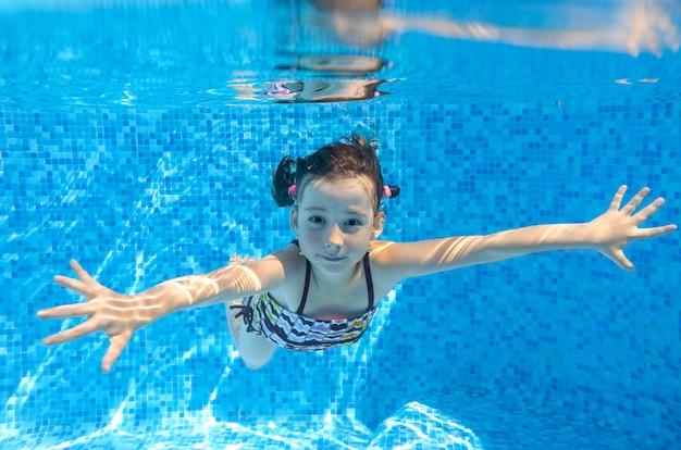 Felice bambino attivo nuota sott'acqua in piscina Foto Premium