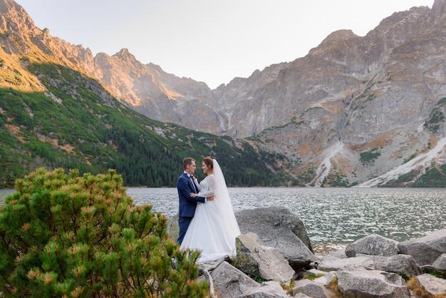 Felice coppia innamorata vestita in abiti da sposa sta quasi baciando con vista mozzafiato sulle montagne e sul lago degli altopiani Foto Gratuite