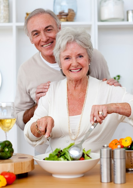 Felice coppia senior eeating un'insalata in cucina Foto Premium