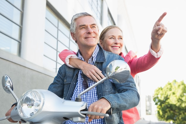 Felice coppia senior in sella a un ciclomotore Foto Premium