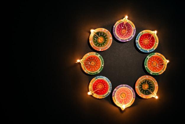 Felice diwali - festival indù, diya tradizionale colorato lampada ad olio su fondo nero Foto Premium