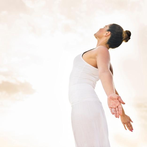 Felice donna facendo yoga sotto il sole Foto Gratuite